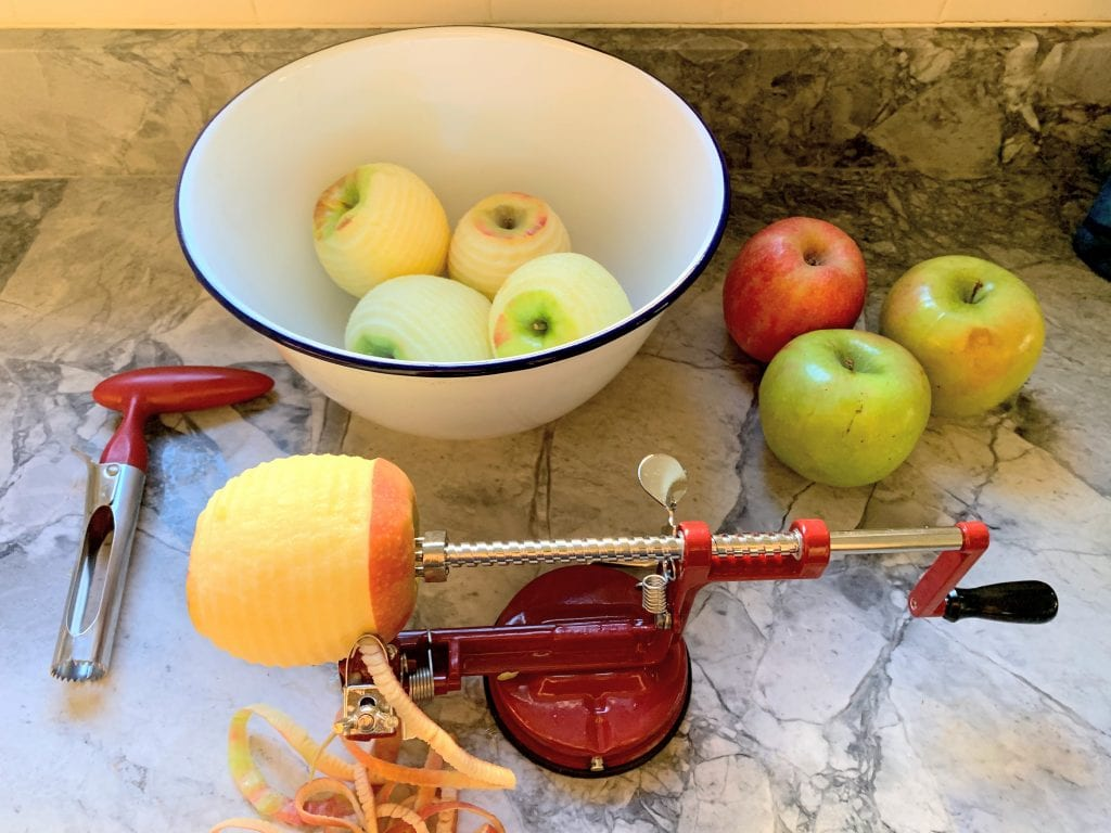 Old fashioned apple peeler and corer with a bowl of peeled apples
