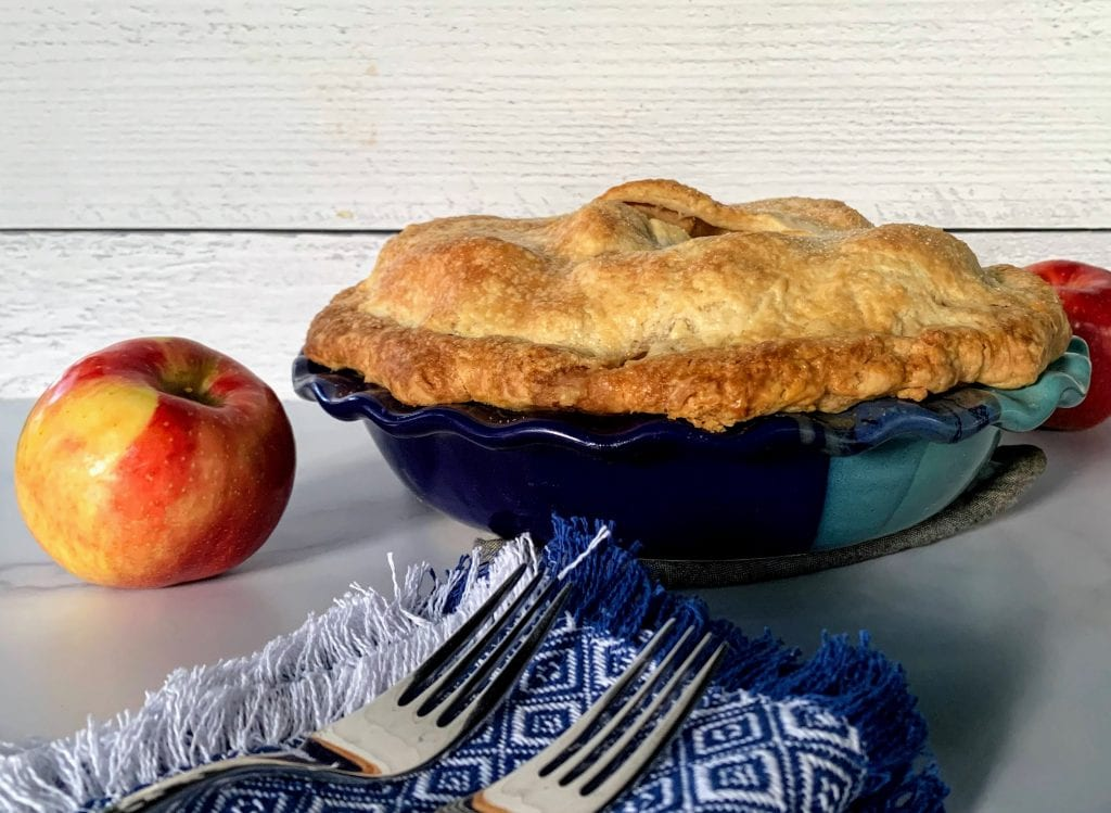 red apples, apple pie in a blue, deep-dish pie plate, and two forks on Mountain Weave style blue and white woven napkins